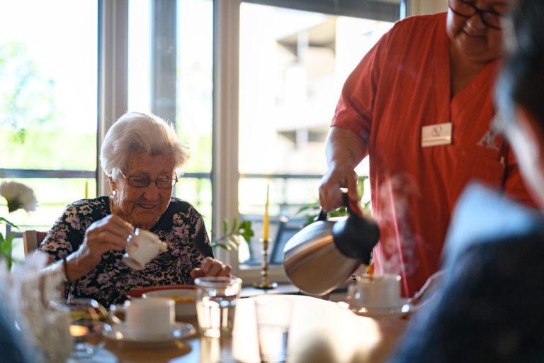 Äldre kvinna fikar tillsammans med andra personer och anställda på A&O