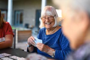 Äldre kvinna som skrattar och spelar kort