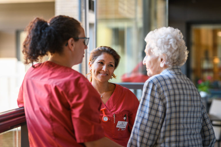 En äldre kvinna pratar med två av de anställda på A&O