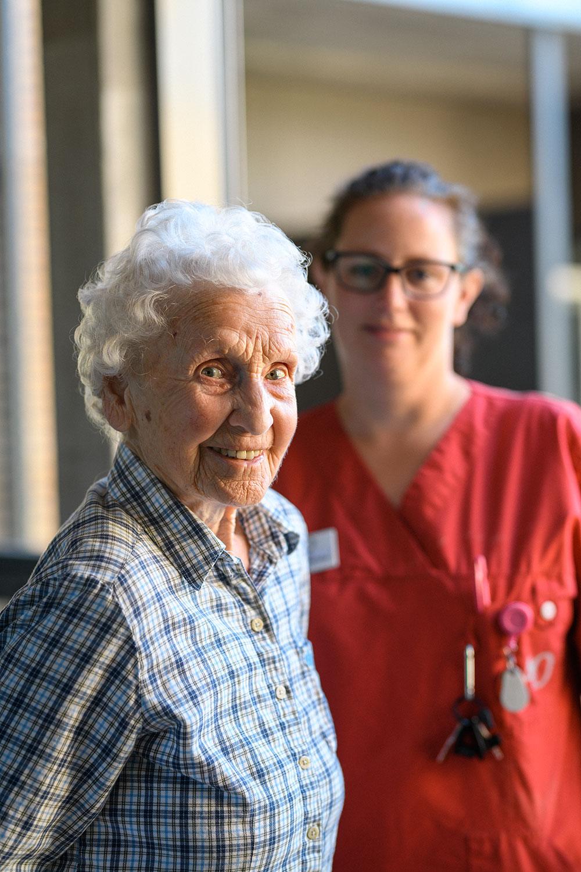 En äldre kvinna kollar in i kameran och ler med en anställd i bakgrunden