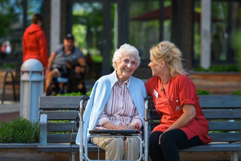 Äldre kvinna utomhus tillsammans med en av de anställda