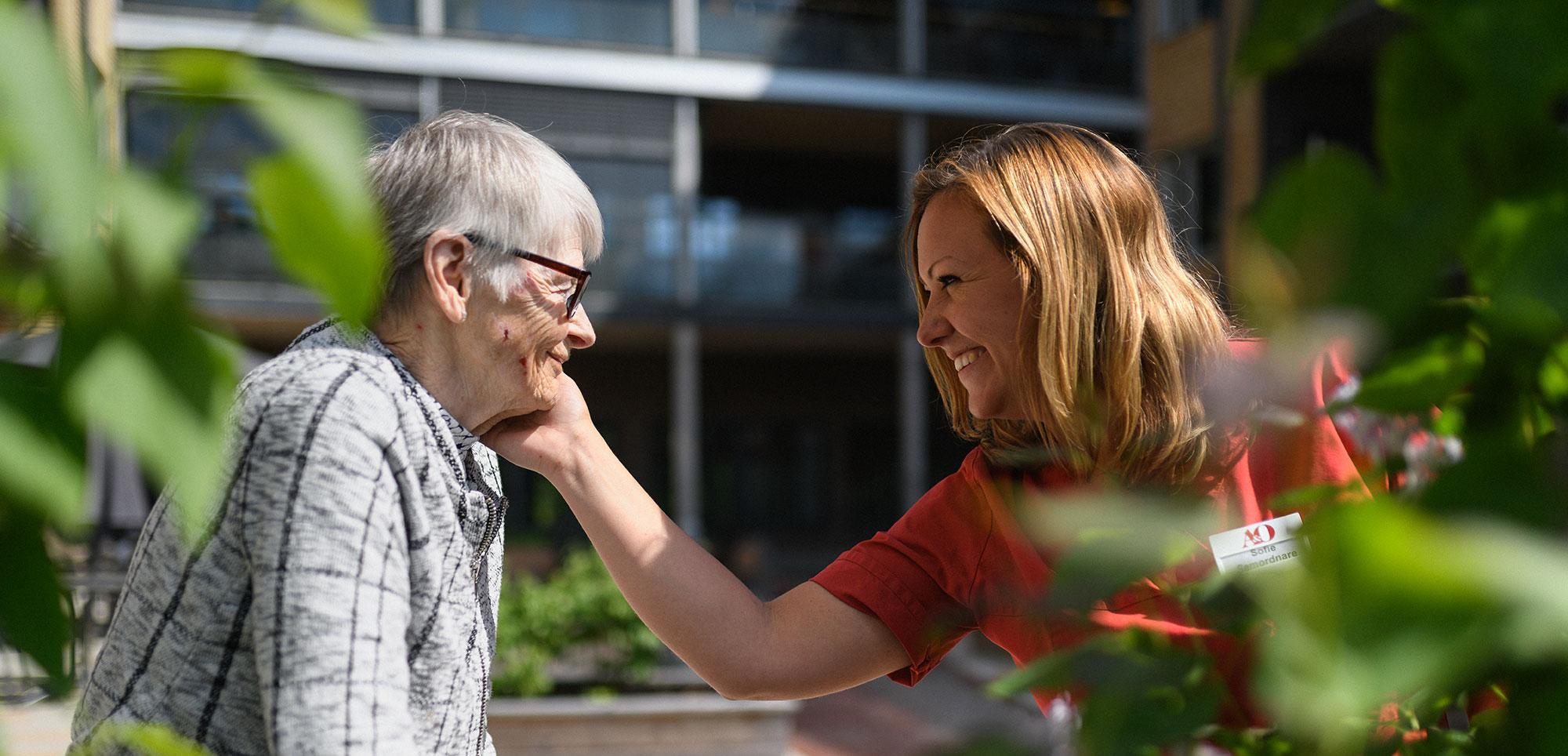 En äldre kvinna och en anställd som är utomhus och ler mot varandra