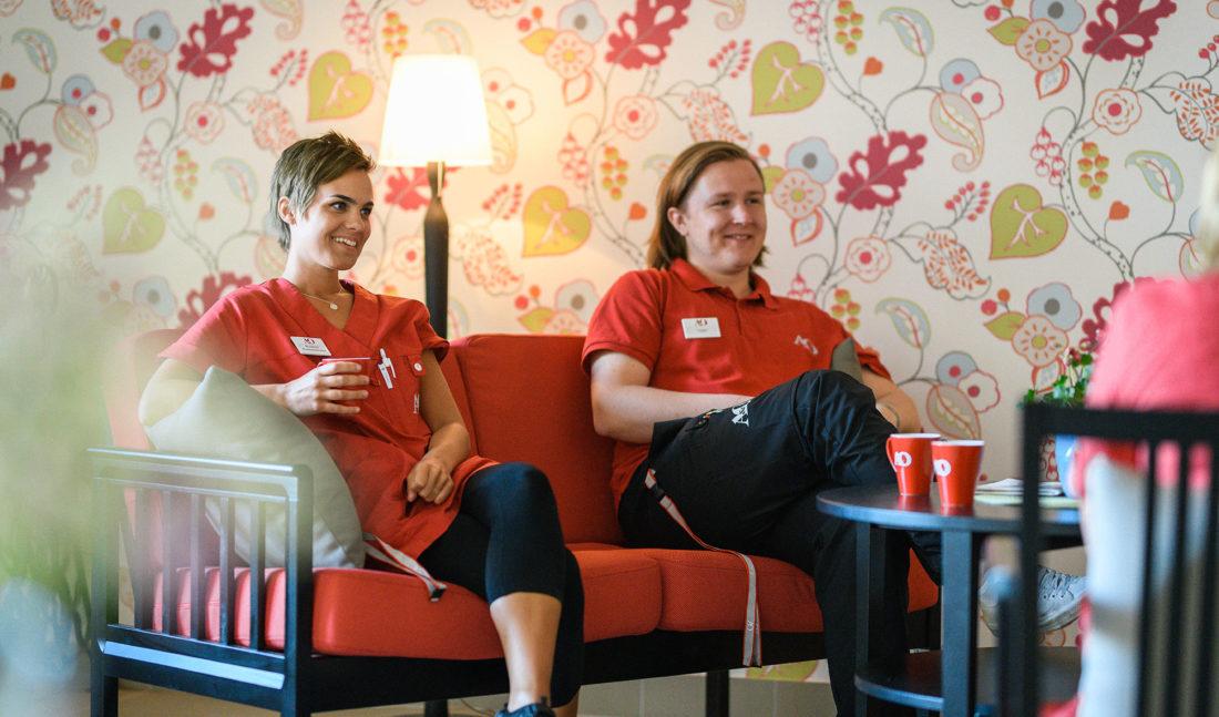 Två av de anställda sitter och dricker kaffe i en soffa