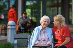 Äldre kvinna utomhus tillsammans med en av de anställda på A&O